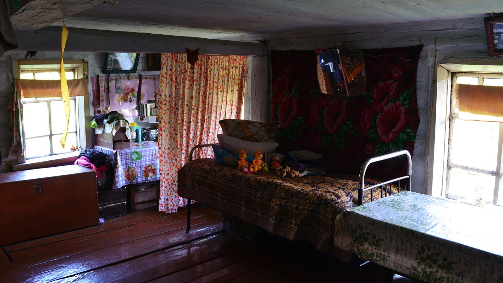 Главная горница с русской печкой в центре и запасной печкой буржуйкой у входа. В противоположном углу горницы телевизор, кухонный стол, сушилка для посуды и еще одна кровать. Вот, в общем-то, и все хозяйство.