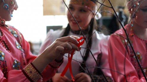 Девушки в национальных костюмах повязвают ленточки
